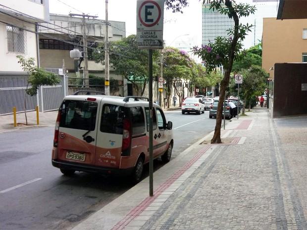 Calçada com piso tátil interrompido por árvores e placa de sinalização