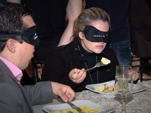 Pessoas jantam com os olhos vendados.