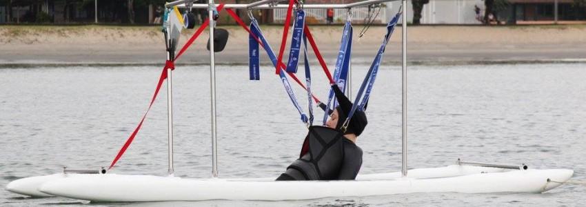 No mar, Mara Gabrilli navega em embarcação adaptada à prática esportiva. Seu corpo está suspenso com auxílio de tiras de segurança atreladas à embarcação.