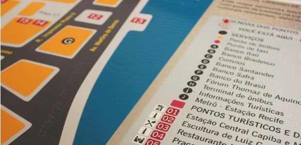 Foto de um mapa tátil, com informações em texto e em braile sobre as ruas de Recife