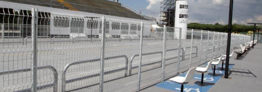 Foto do Sambódromo do Anhembi vazio à luz do dia com cadeiras reservadas às pessoas com deficiência.