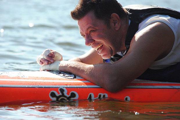 Foto do Alan sorrindo. Ele é branco, tem cabelos curtos e está deitado em uma prancha no mar.