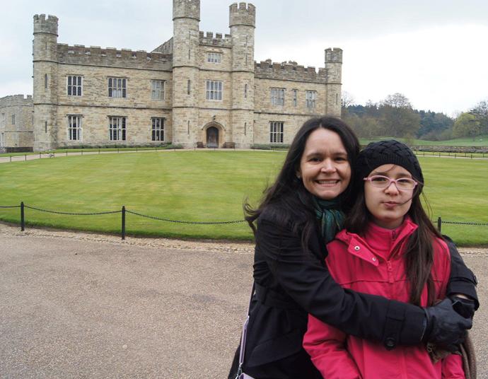 Foto da Cristina ao lado da sua filha Milena. Cristina é morena e tem cabelos longos. Milena é uma criança morena e tem cabelos longos. Ao fundo, há um castelo.