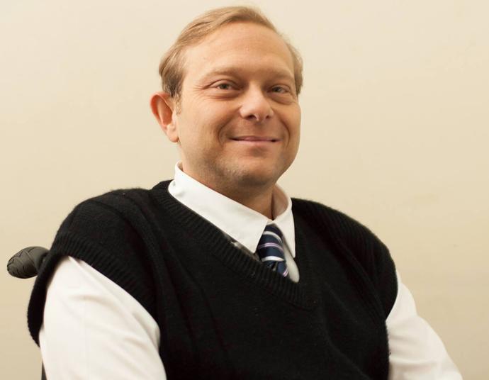 Foto do Luis sorrindo. Ele é jovem, loiro, tem cabelos curtos e usa uma camisa social branca com gravata e um colete preto por cima.