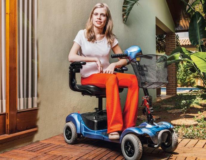 Foto da Nathalia sorrindo. Ela é loira e tem cabelos longos. Nathalia está sentada em uma cadeira motorizada, no ambiente externo de uma casa.