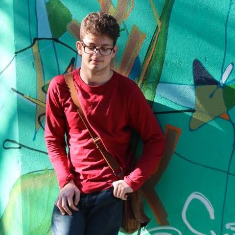 Foto do Victor. Ele é branco, usa óculos e usa blusa vermelha e está encostado em um muro colorido e grafitado.