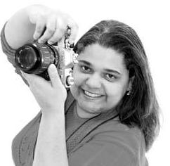 Kica de Castro faz pose para foto e segura uma câmera fotográfica