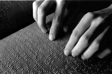 Dedos passam em papel com braille