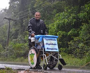 Zé do Pedal empurra cadeira de rodas em estrada rodeada de floresta