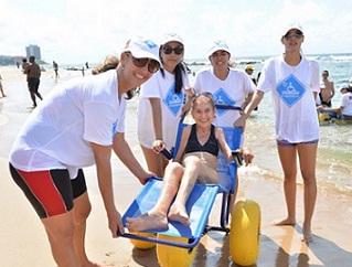 Pessoas seguram cadeira anfíbia flutuante na praia