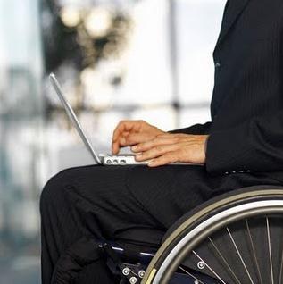 Foto de um cadeirante com terno mexendo em um notebook