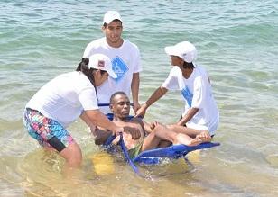 Pessoas seguram cadeira anfíbia no mar com uma pessoa com deficiência