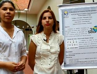 Foto de duas alunas e um cartaz da faculdade