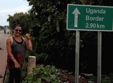 Foto de Jéssica ao lado de uma placa indicando Uganda
