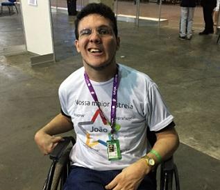 Foto de João Santiago sorrindo em sua cadeira de rodas