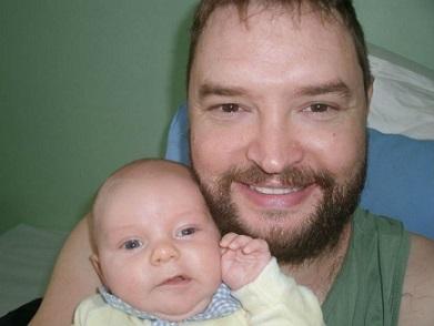 Foto de Jonas sorrnido com seu filho no colo