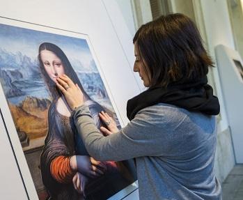 Foto de uma mulher cega tocando réplica do quadro da Monalisa