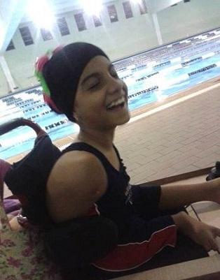 Foto de Laura sorrindo em sua cadeira de rodas
