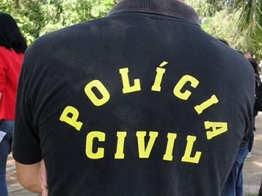 Foto de um homem de costas com a camisa da Polícia Civil