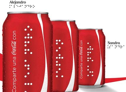 Foto de três latinhas da marca escritas em braille