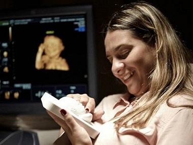 Foto de uma mãe sentindo a reprodução do ultrassom