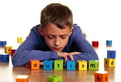 Criança autista sentada em frente a um brinquedo de montar