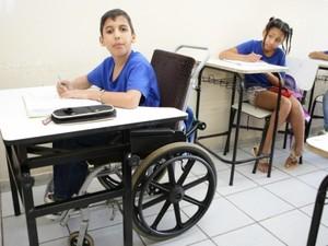 Criança em cadeira de rodas na sala de aula à frente do PC