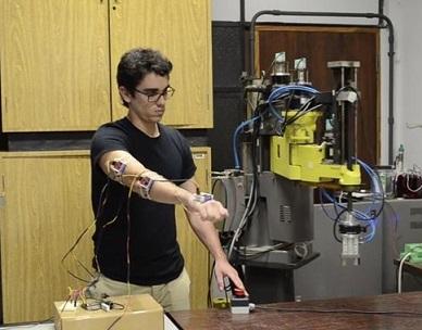 Foto de Vinícius testando seu braço mecânico