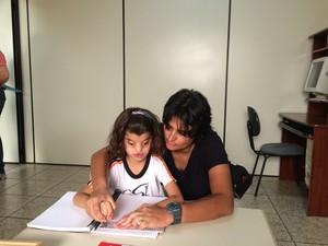 Foto de Yasmin e sua mãe lendo braile