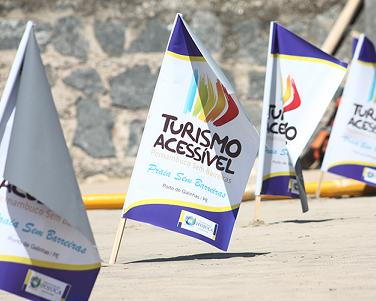 Foto de bandeiras do Turismo Acessível na areia