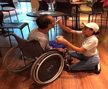 Foto de Lauane ajoelhada dando sorvete ao cliente
