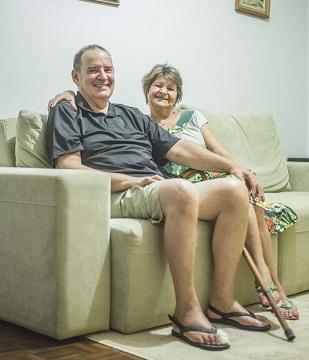 Imagem de um casal de idosos sentados no sofá