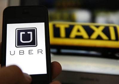 Foto do aplicativo Uber e um táxi ao fundo