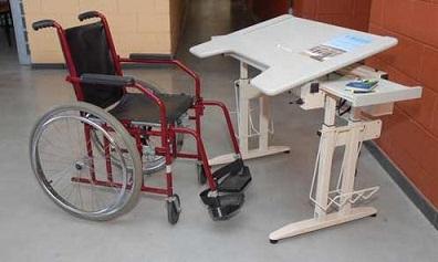 Foto de uma cadeira de rodas em frente a uma mesa escolar