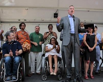 Foto do prefeito Bill e de pessoas ao lado em um palco