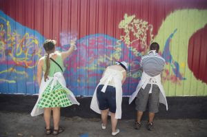 Jovens pintando um tapume bem colorido