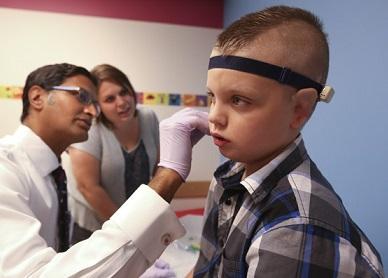 Foto de Elijah e um médico examinando sua orelha