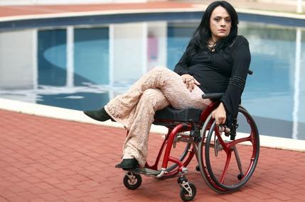 Adriana Buzelin está em sua cadeira de rodas, à beira de uma piscina.
