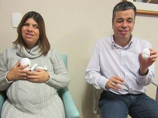 Camila e seu marido seguram modelos do filho feitos em impressora 3D