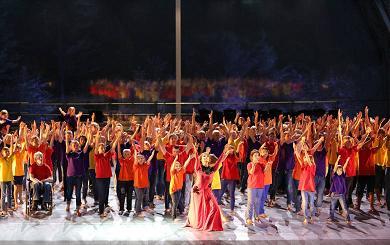Diversas pessoas em um palco, com os braços erguidos.