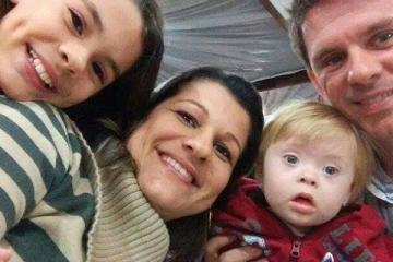 Gustavo, criança com síndrome de Down, com seus pais e sua irmã