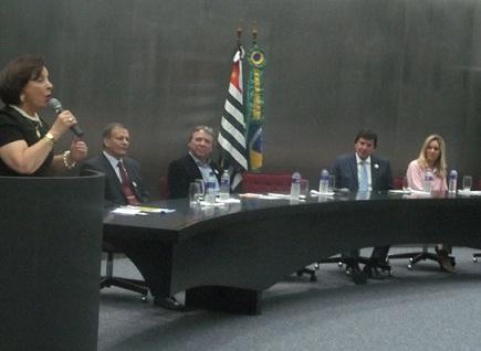 Dra. Linamara Rizzo Battistella segurando microfone em frente púlpito