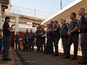 Grupo de policiais militares observa as instruções do professor
