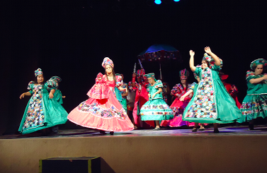 Mulheres com síndrome de Down dançam no palco com vestidos longos