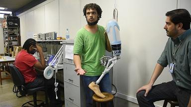 Homem de camisa verde segura uma prótese de perna