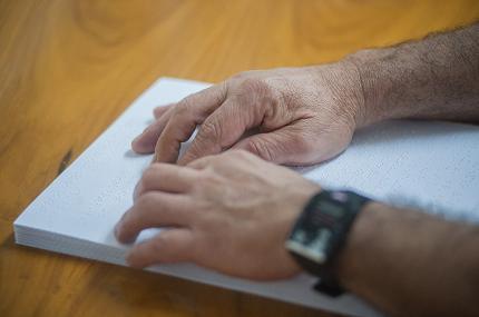 Mãos tateiam texto em braile sobre uma mesa de madeira