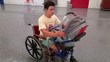 Alden sentado em cadeira de rodas segurando carrinho de bebê acoplado