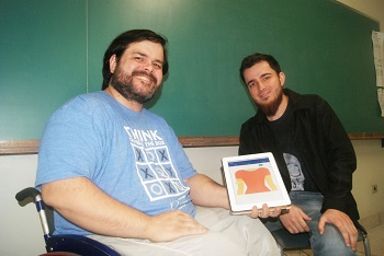 Rodrigo e Victor seguram um tablet com o aplicativo na tela