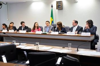 Participantes da discussão estão sentados atrás de uma mesa comprida