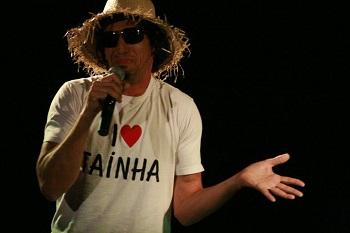 Comediante usa chapéu de palha, óculos escuros e camisa branca